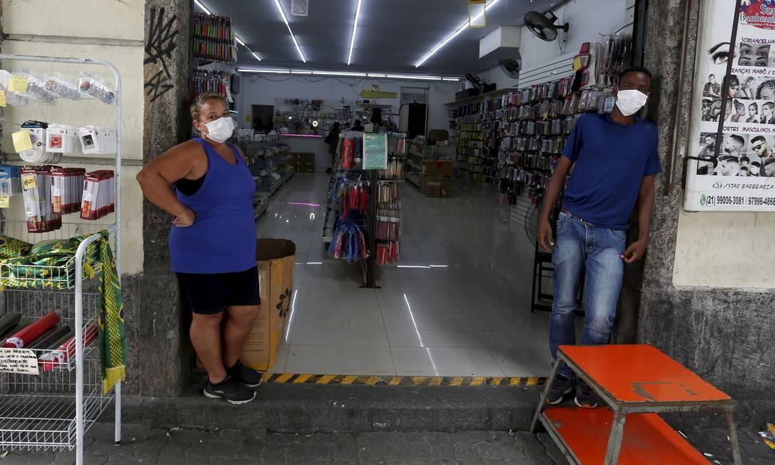 Funcionários trabalham de máscaras na Rua Buenos Aires, no Centro Foto: Fabiano Rocha