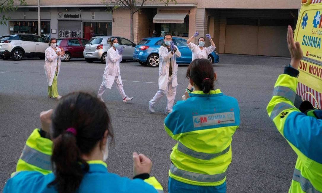 Funcionários da área de saúde são aplaudidos em Madri, na Espanha: mortes por coronavírus começam a cair no país Foto: HANDOUT / AFP