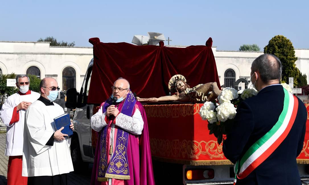 Um padre usando uma máscara reza ao lado do prefeito de Cernusco sul Naviglio, Ermanno Zacchetti, em um cemitério, em homenagem às vítimas Foto: FLAVIO LO SCALZO / REUTERS