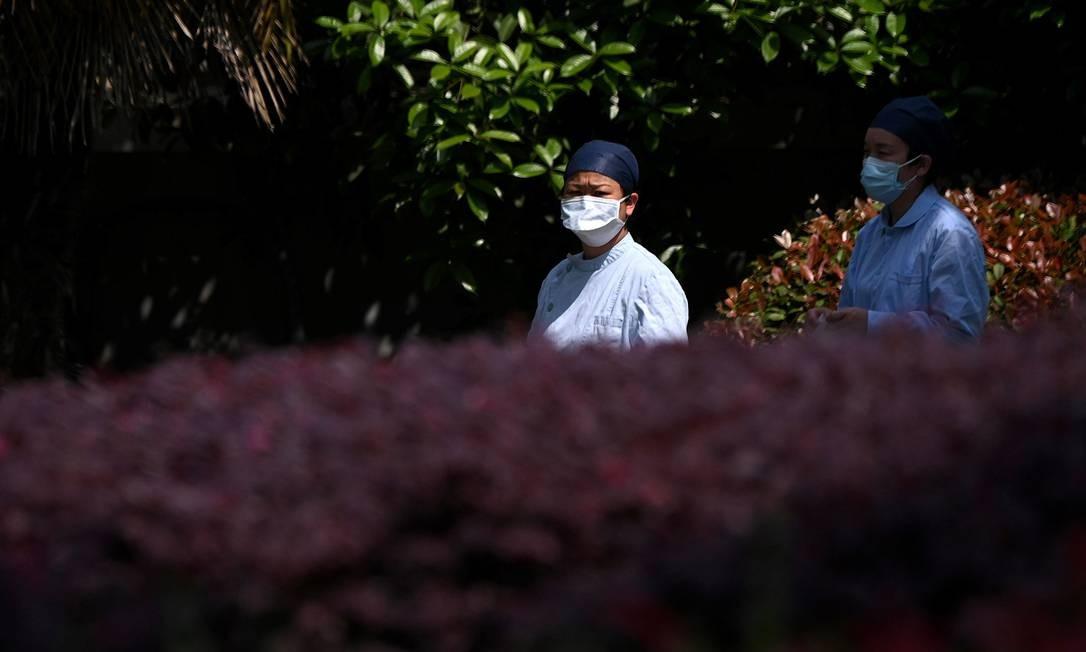 Enfermeiras usando máscaras caminham do lado de fora do hospital Wuhan Jinyintan na província de Hubei Foto: NOEL CELIS / AFP/09-04-2020