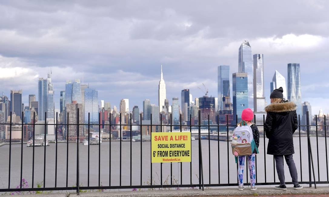 Mãe e filha olham para Manhattan, ao lado de um dos muitos cartazes de distanciamento social recentemente colocados em Weehawken, Nova Jersey Foto: Michael loccisano / AFP