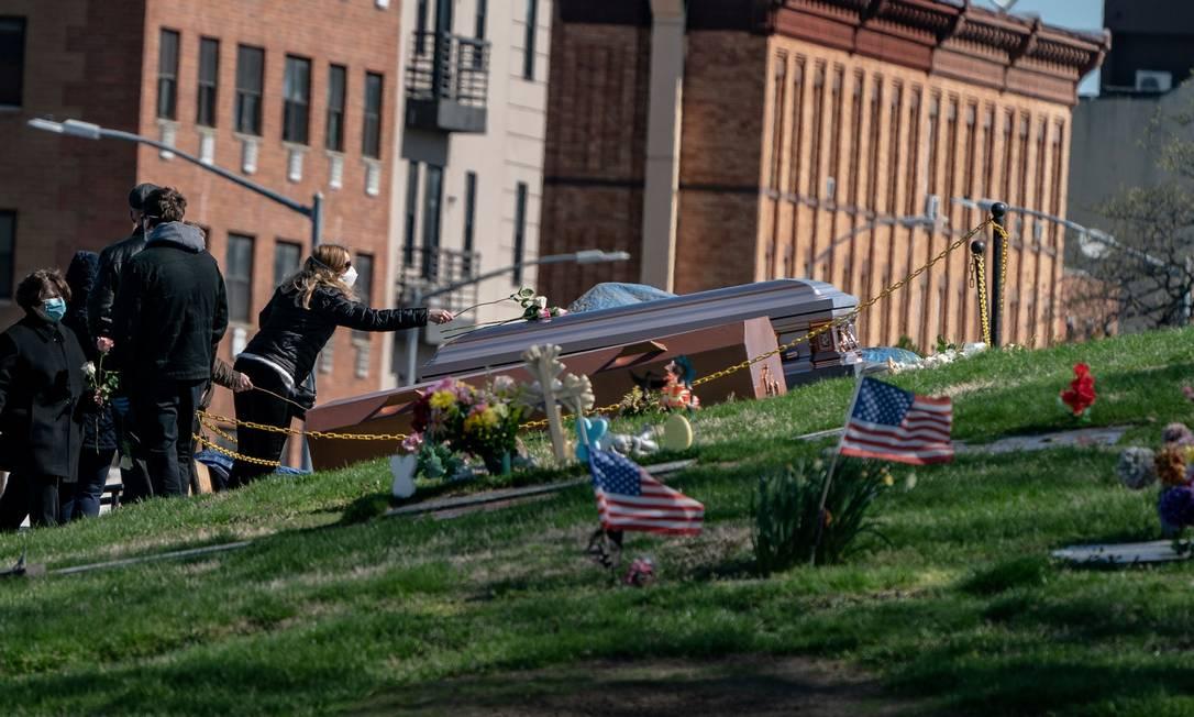 Com máscaras, americanos participam de funeral em cemitério no Brooklyn, em Nova York, durante o surto do coronavírus Foto: JEENAH MOON / REUTERS