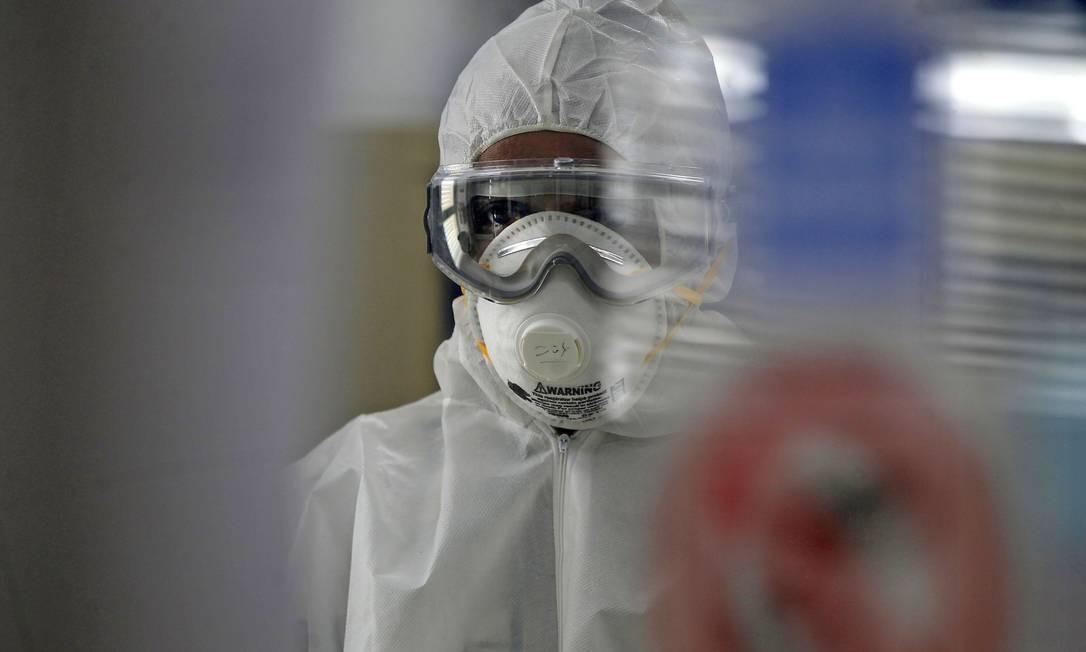 Técnico testa componentes em busca de um controle para pandemia do coronavírus Foto: MOHAMMED HUWAIS/AFP