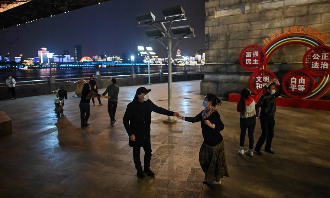Casais dançam em um parque em Wuhan, cidade que registrou os primeiros casos da Covid-19 Foto: HECTOR RETAMAL / AFP