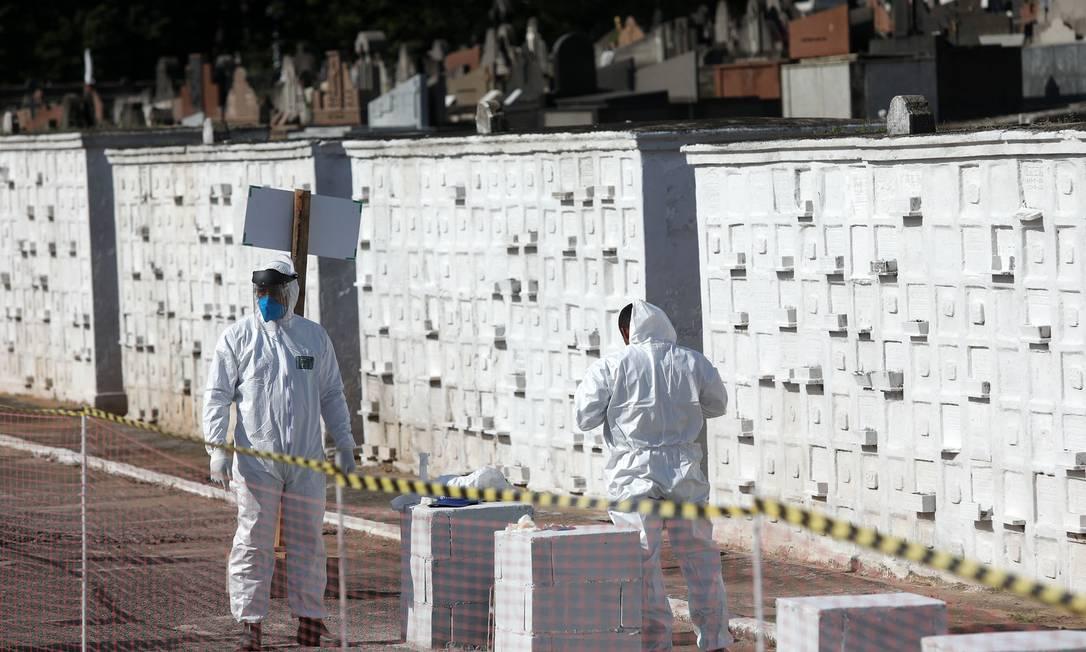 Sepultadores colocam EPI para executar o enterro de vítima da Covid-19 Foto: Fábio Motta : Fabio Motta / Agência O Globo