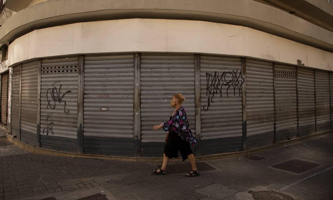 Mulher com máscara protetora caminha por ruas vazias do centro do Rio Foto: Gabriel Monteiro / Agência O Globo