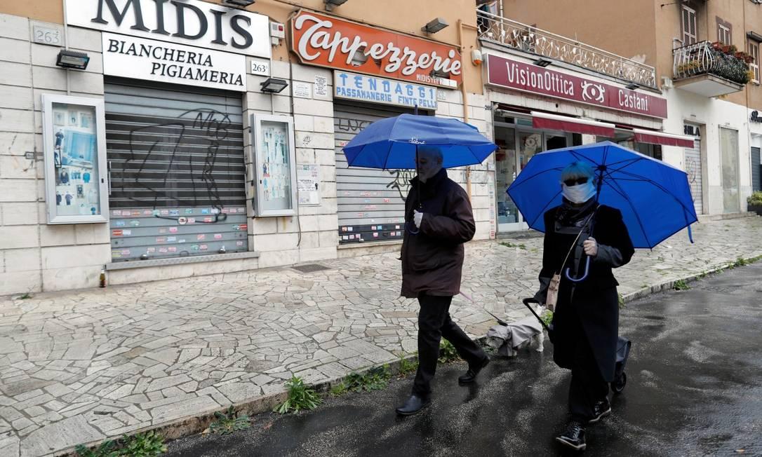 Em Roma, pedestres caminham em frente a lojas fechadas Foto: YARA NARDI / REUTERS