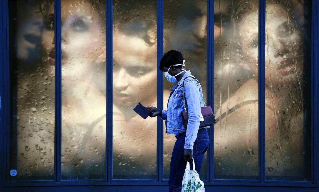 Mulher caminha pelas ruas de Paris com máscara: artigo seguirá tendo exportação restrita pela União Europeia Foto: ALAIN JOCARD / AFP