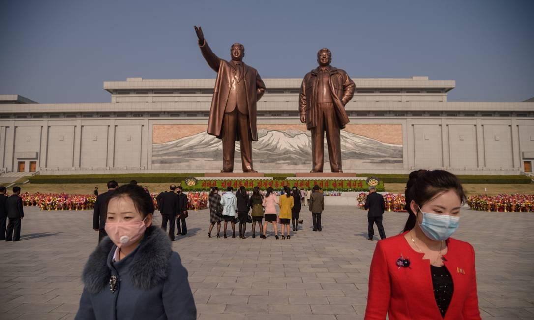 Pessoas com máscaras deixam flores na estátua de Kim Il Sung. Foto: KIM WON JIN / AFP
