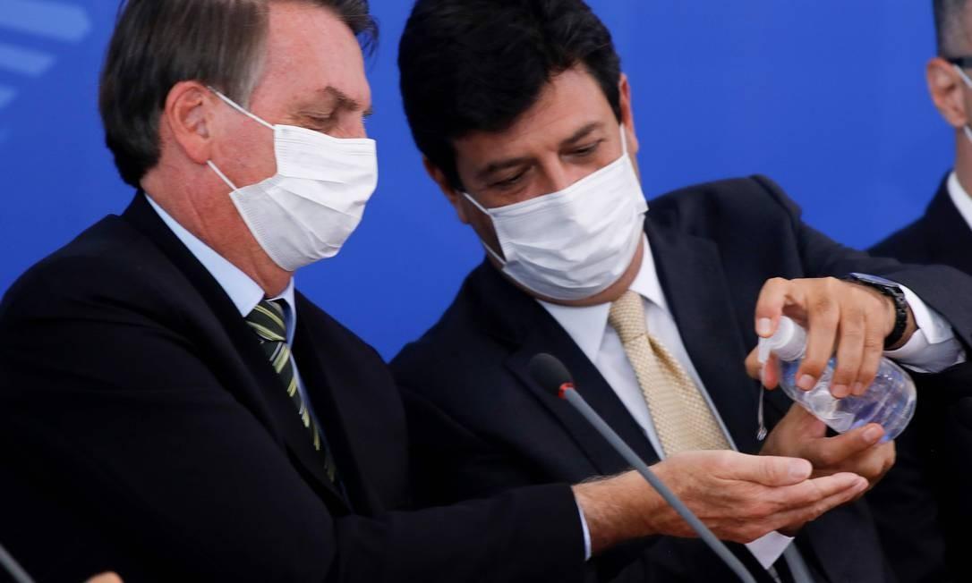 Durante a coletiva, Mandetta também aplicou álcool gel nas mãos do presidente Foto: SERGIO LIMA / AFP - 18/03/2020