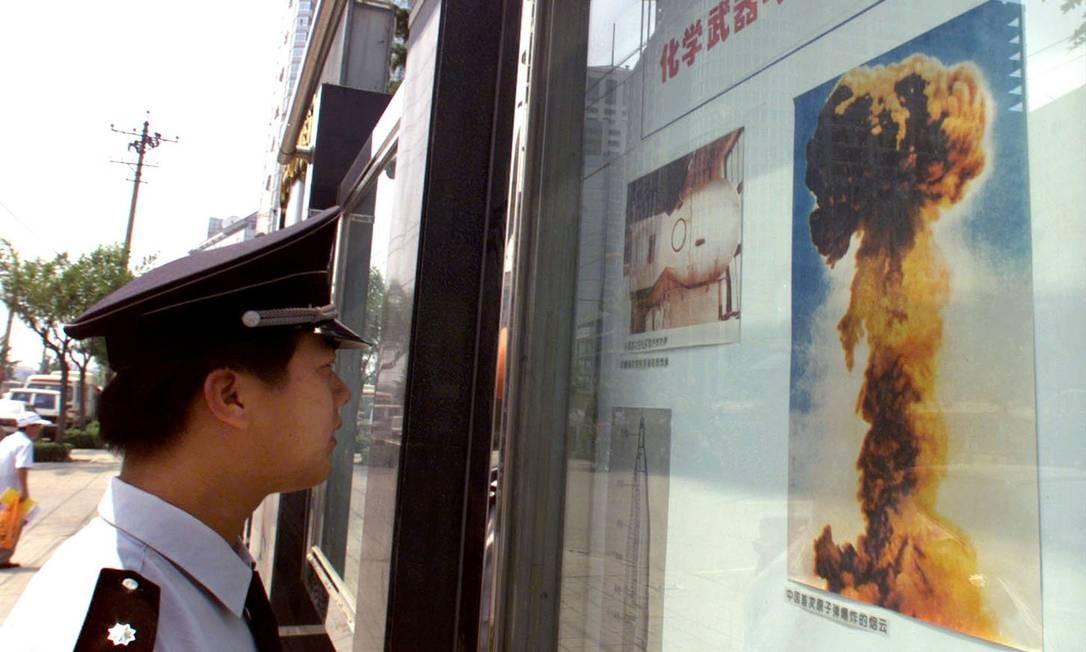 Homem observa imagem de detonação de bomba nuclear chinesa em um quadro informativo no centro de Pequim Foto: Andrew Wong / Reuters