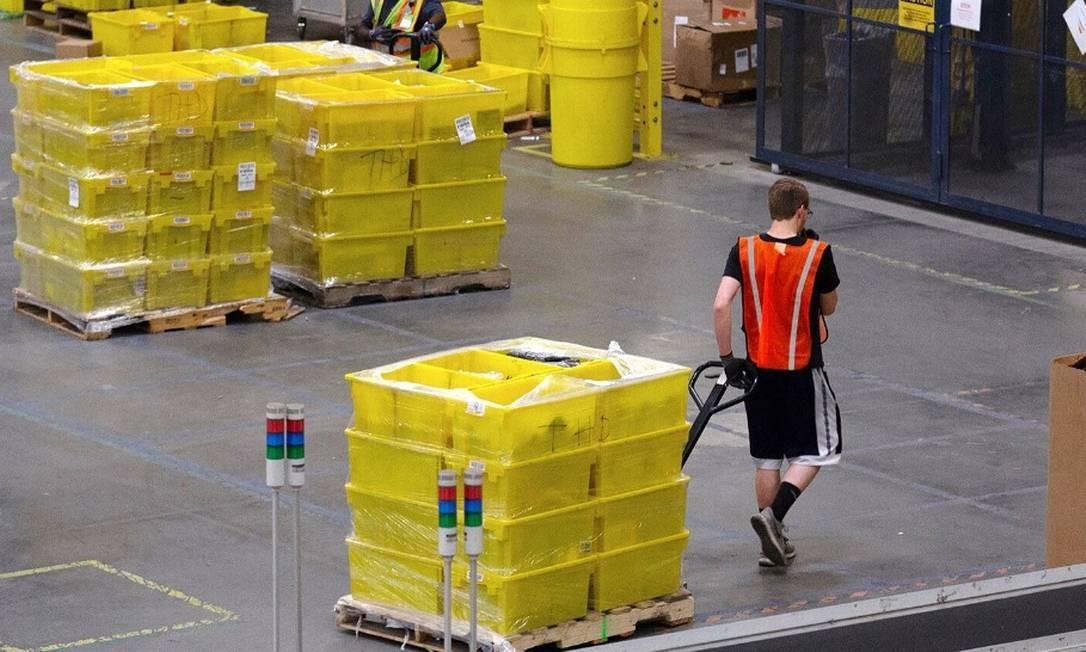 Funcionário puxa um carrinho com mercadorias em um dos armazéns da Amazon Foto: Bloomberg