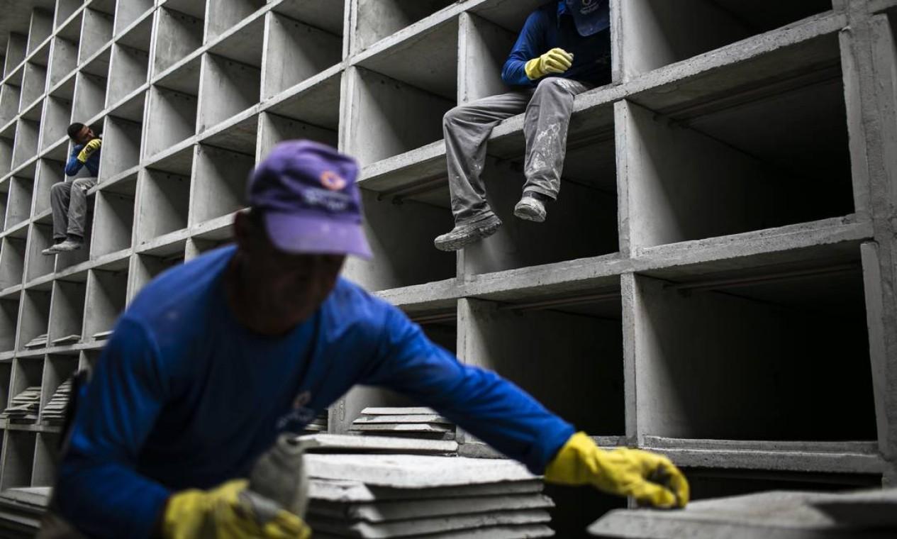 Funcionários trabalham na construção de novas gavetas, no Cemitério do Caju, destinadas a vítimas da Covid-19 Foto: Hermes de Paula / Agência O Globo