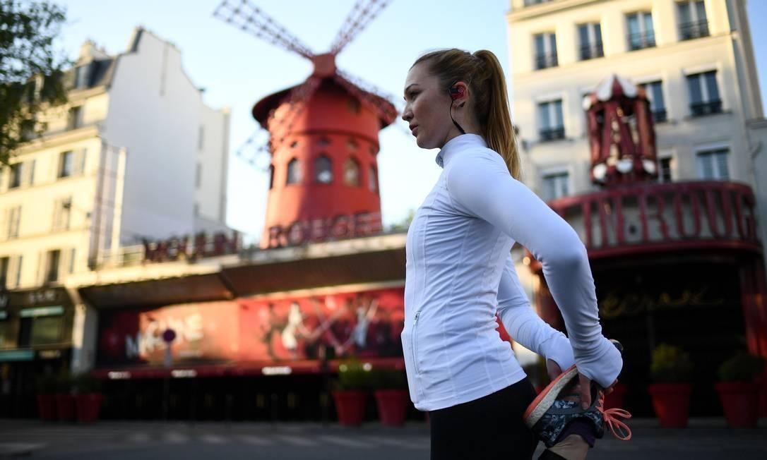 Mathilde, dançarina do Moulin Rouge, se alonga antes de se exercitar em frente à famosa casa de espetáculo em Paris Foto: FRANCK FIFE / AFP
