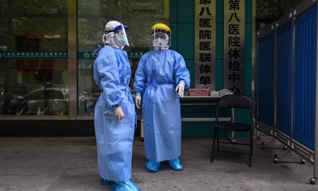 Médicos com equipamento de proteção em centro de testagem para a Covid-19 em Wuhan Foto: HECTOR RETAMAL / AFP