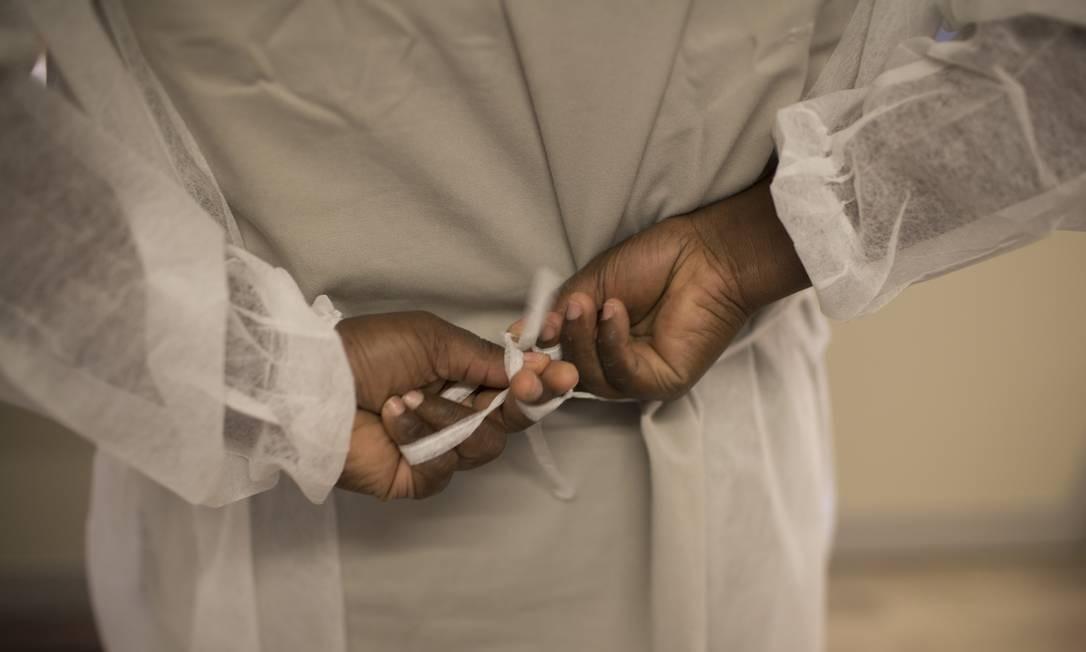 Funcionária termina de amarrar o capote descartável, um dos últimos itens de proteção a ser vestido Foto: Márcia Foletto / Agência O Globo