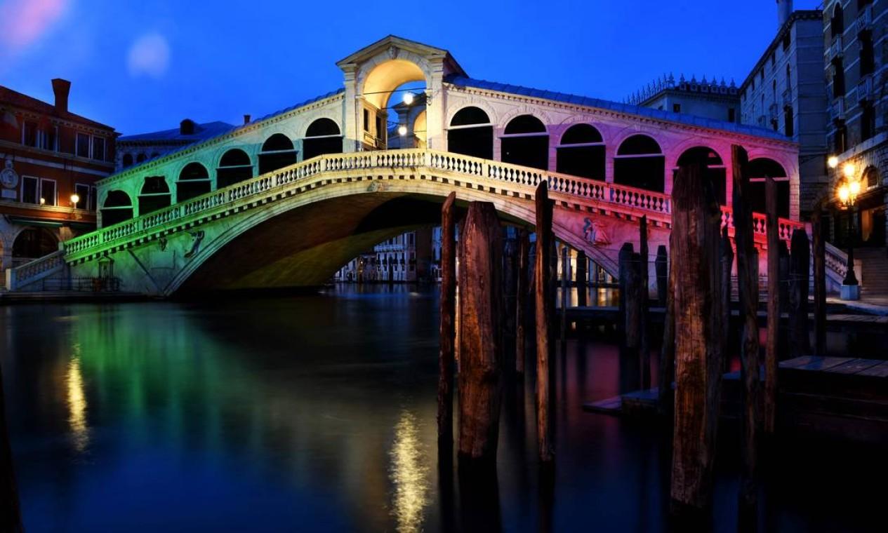 As cores da bandeira italiana são projetadas na ponte Rialto, em Veneza, como um sinal de esperança enquanto toda a Itália ainda enfrenta os efeitos da propagação do novo coronavírus Foto: ANDREA PATTARO / AFP