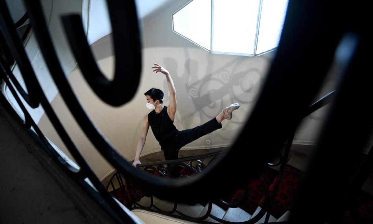 O dançarino de balé chinês Chun Wing Lan pratica com uma máscara protetora na escada de seu prédio, em Paris, no 31º dia de um duro bloqueio que visa coibir a propagação da pandemia na França Foto: FRANCK FIFE / AFP - 15/04/2020