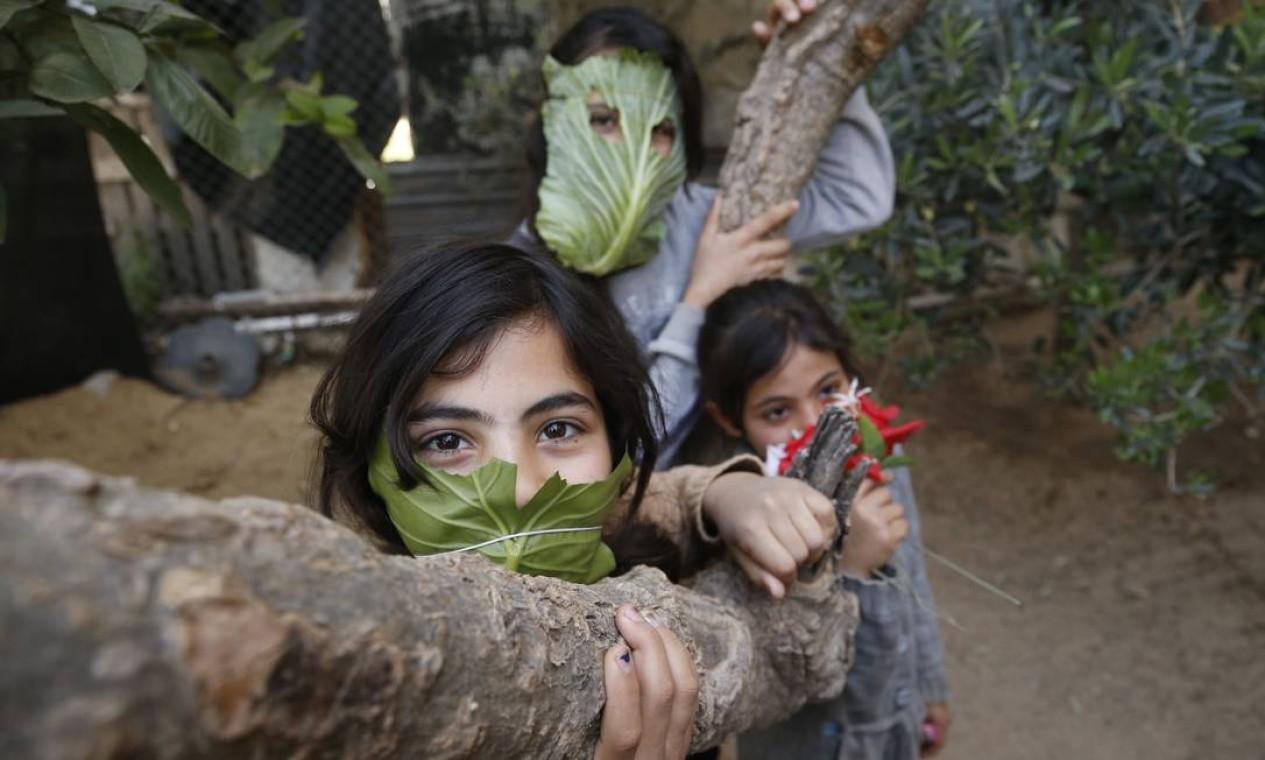 Crianças palestinas usam máscaras improvisadas feitas de folhas de repolho em Beit Lahia, no norte da Faixa de Gaza, em meio à pandemia de Covid-19. Foto: MOHAMMED ABED / AFP - 16/04/2020
