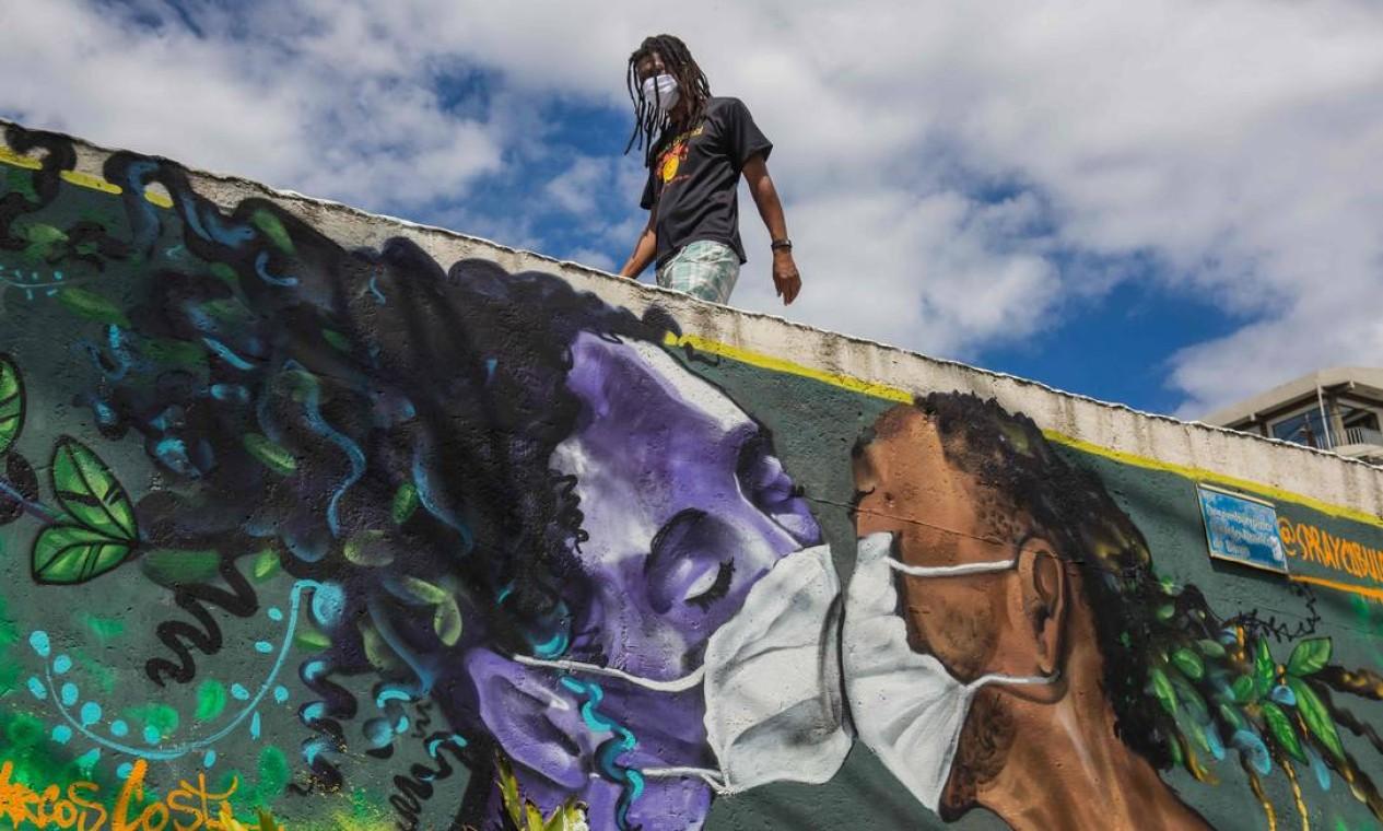 Homem usando máscara facial passa por um grafite do artista Marcos Costa, ou Spraycabuloso, na entrada da favela Solar de Unhao, em Salvador, Bahia Foto: ANTONELLO VENERI / AFP - 15/04/2020