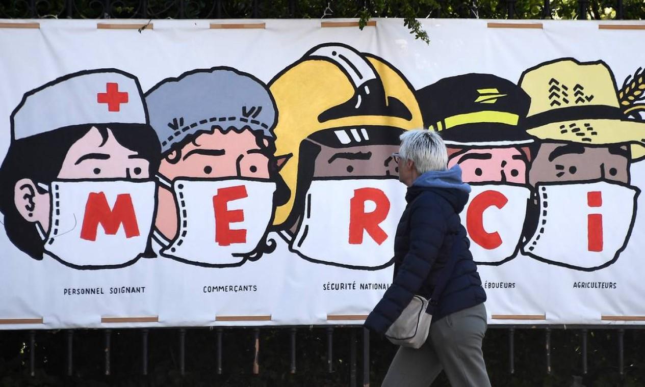 Uma pessoa passa por um pôster agradecendo aos profissionais de saúde, lojistas, segurança nacional francesa, funcionários dos correios e agricultores, em Paris Foto: FRANCK FIFE / AFP - 14/04/2020