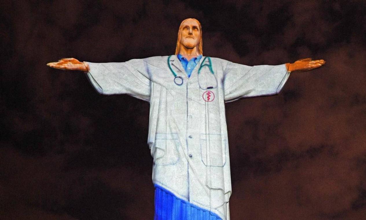 A famosa estátua do Cristo Redentor, no Domingo de Páscoa, no Rio de Janeiro, recebe a projeção de um uniforme médico em homenagem a toda a equipe médica que luta contra a pandemia de coronavírus em todo o mundo Foto: CARL DE SOUZA / AFP - 12/04/2020