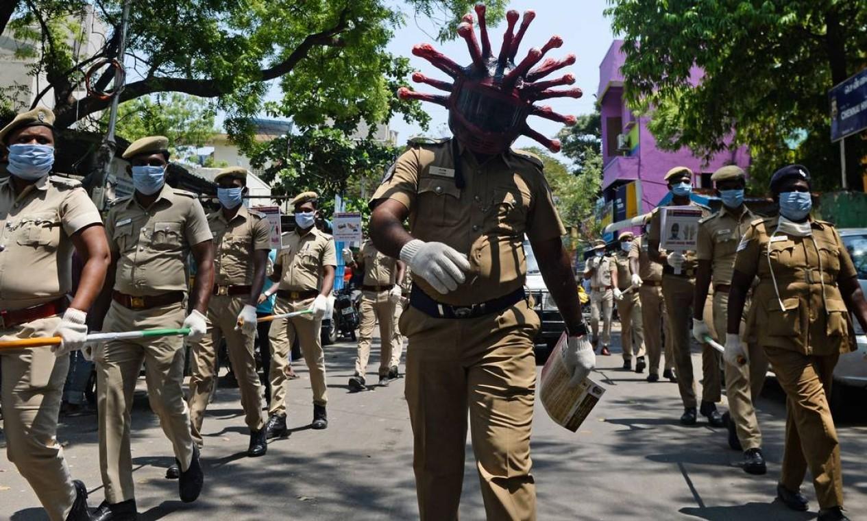 Policial usa capacete de coronavírus enquanto participa de uma procissão para conscientizar sobre o a pandemia em Chennai, na Índia Foto: ARUN SANKAR / AFP - 12/04/2020