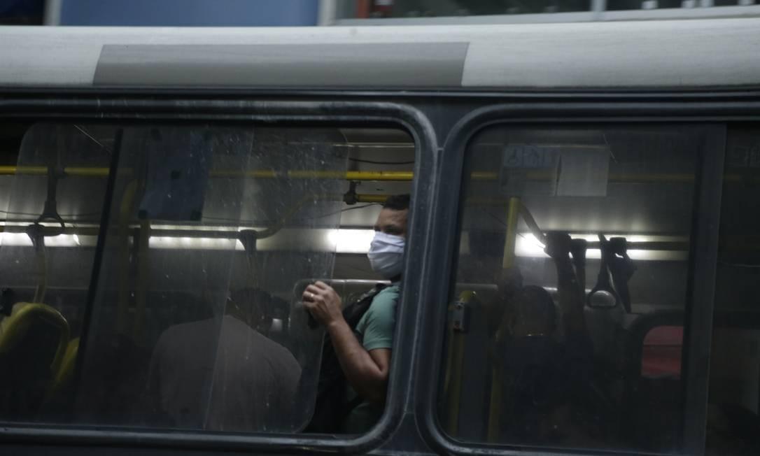 Nos ônibus, houve quem se aventurasse com as pequenas frestas abertas nas janelas Foto: Antonio Scorza / Antonio Scorza