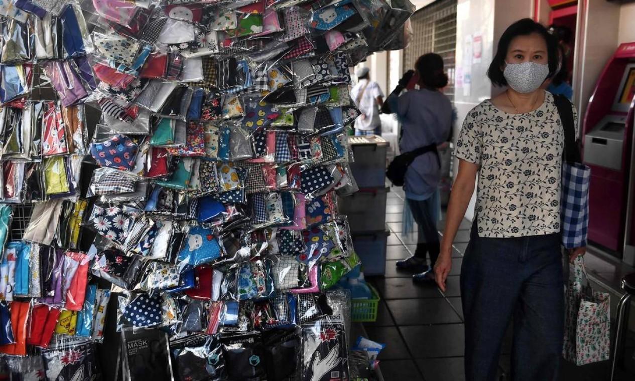 Uma mulher usa uma máscara facial, como medida preventiva contra a disseminação do novo coronavírus, enquanto passa por uma barraca vendendo máscaras de pano em um mercado ao ar livre em Bangkok, na Tailândia Foto: LILLIAN SUWANRUMPHA / AFP