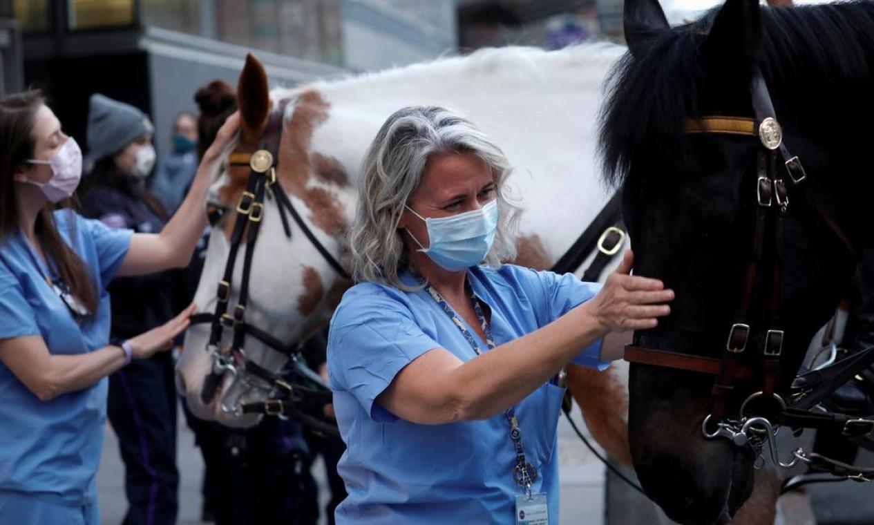 Michele Pottberg, uma enfermeira do NYU Langone Medical Center, acaricia um cavalo do Departamento de Polícia de Nova York do lado de fora do hospital, em Manhattan. A Polícia Montada e outras unidades foram à unidade aplaudir e agradecer aos profissionais de saúde que atuam durante o surto da Covid-19 na cidade de Nova York Foto: MIKE SEGAR / REUTERS - 16/04/2020