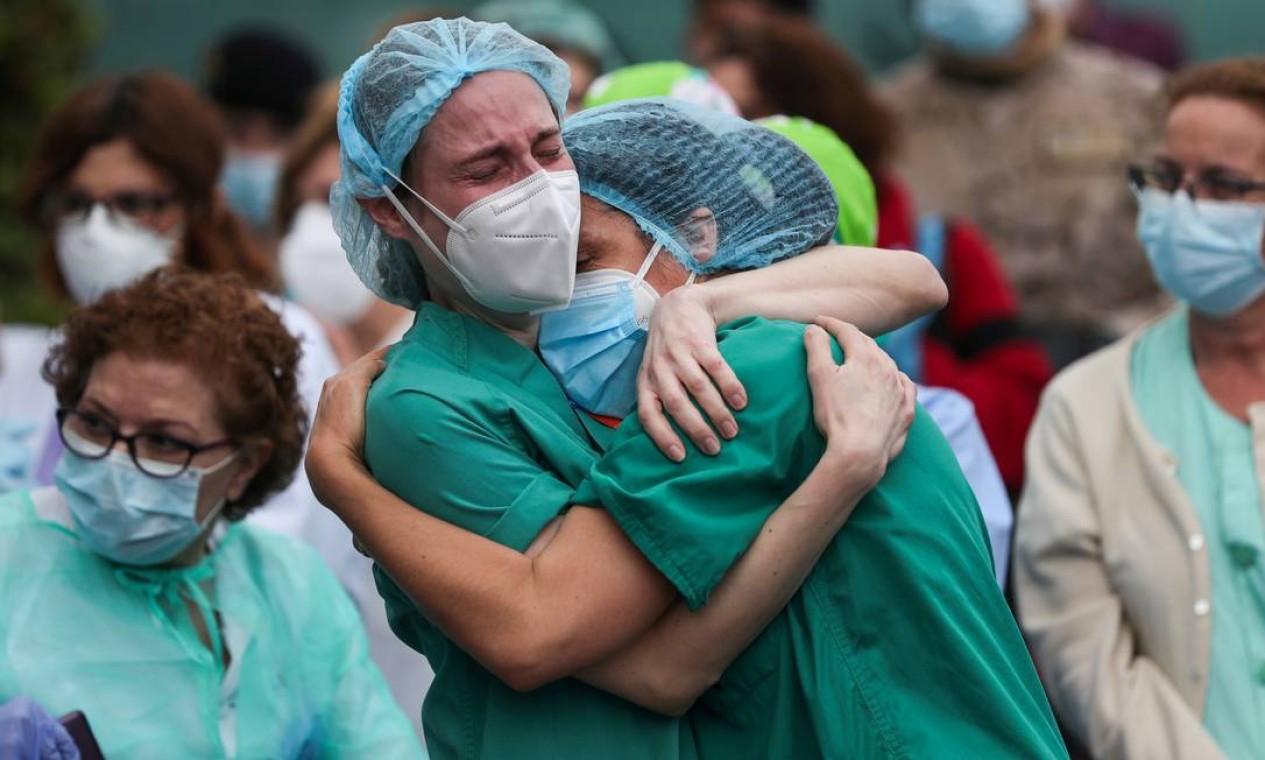 Profissionais de saúde se abraçam durante uma homenagem a um enfermeiro que morreu devido à Covid-19 em meio ao surto de doença, em frente ao Hospital Severo Ochoa, em Leganes, Espanha Foto: SUSANA VERA / REUTERS - 13/04/2020