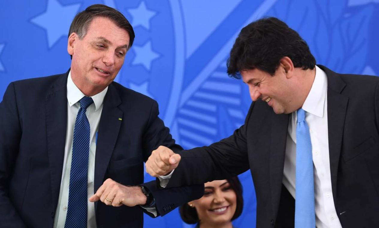 O presidente Jair Bolsonaro e o ministro da Saúde, Luiz Henrique Mandetta, cumprimentam-se durante a cerimônia de posse do novo ministro da Saúde, Nelson Teich, no Palácio do Planalto, em Brasília Foto: EVARISTO SA / AFP - 17/04/2020