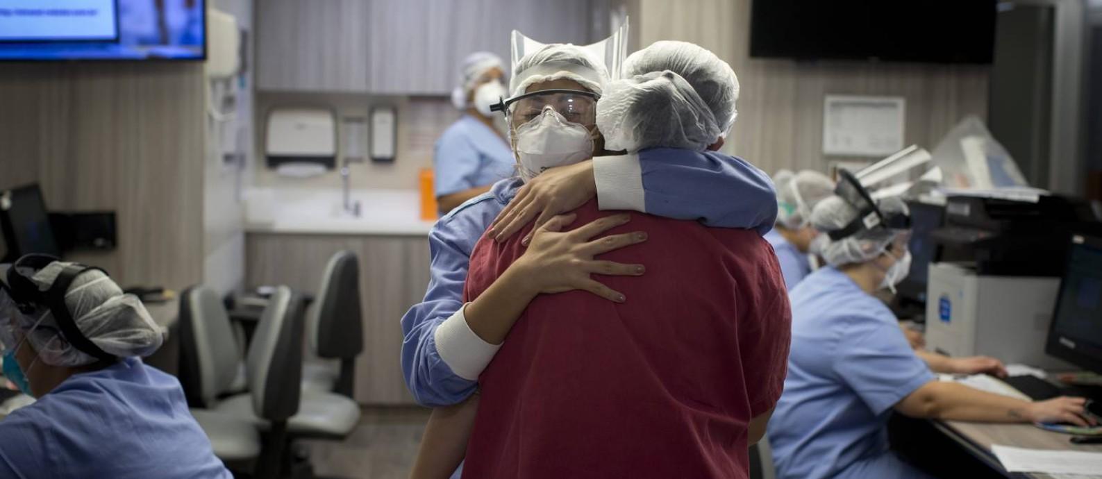 O abraço de uma enfermeira e uma técnica, que reconheciam o cansaço uma da outra e trocavam impressões sobre os riscos e a evolução da doença nas ruas. Foto: Márcia Foletto / Agência O Globo