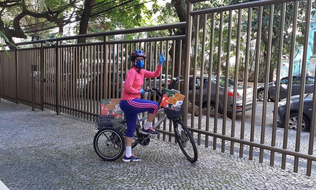 De bicicleta e toda paramentada, Gisela de Castro leva aos clientes seus livros infantis autografados Foto: Divulgação