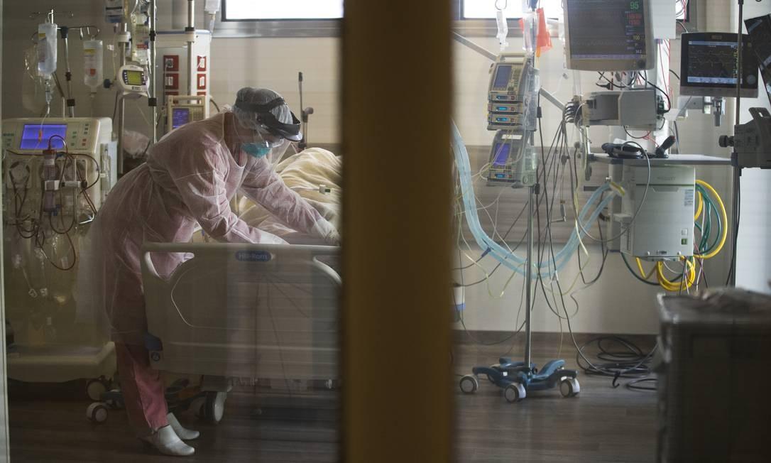 Enfermeira cobre paciente que está internada na UTI com coronavírus Foto: Márcia Foletto / Agência O Globo