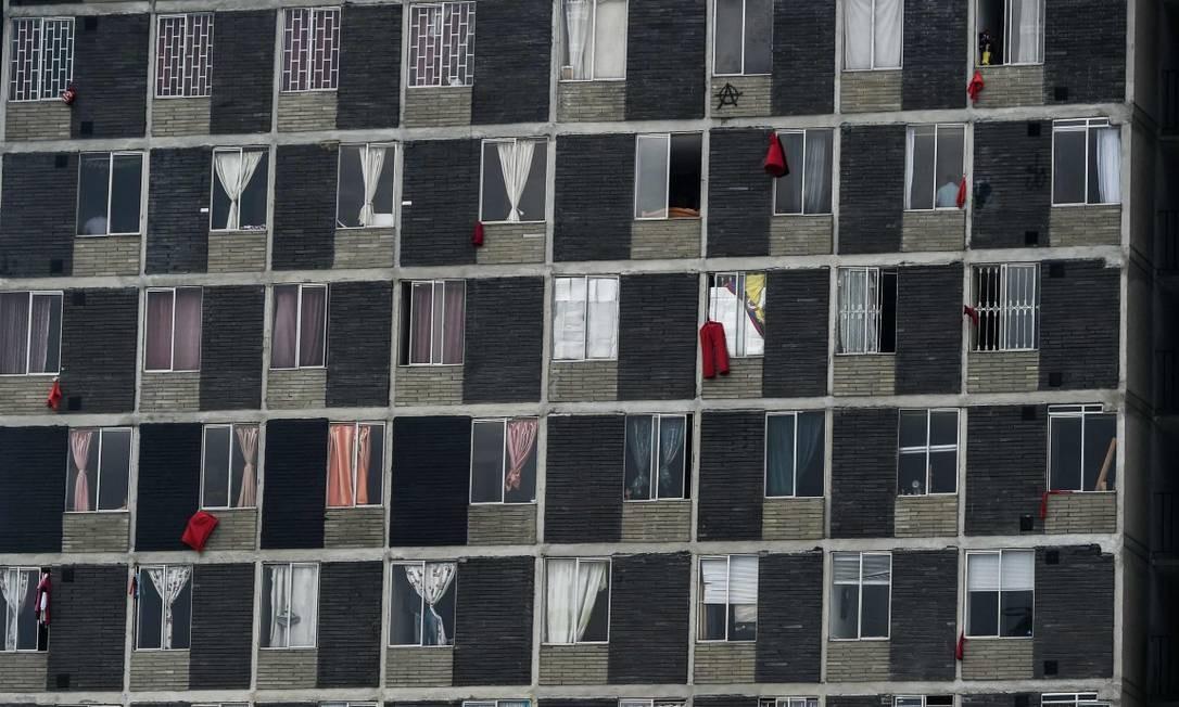 Moradores de Bogotá penduram bandeiras vermelhas em suas janelas como pedido de ajuda Foto: JUAN BARRETO / AFP/15-04-2020