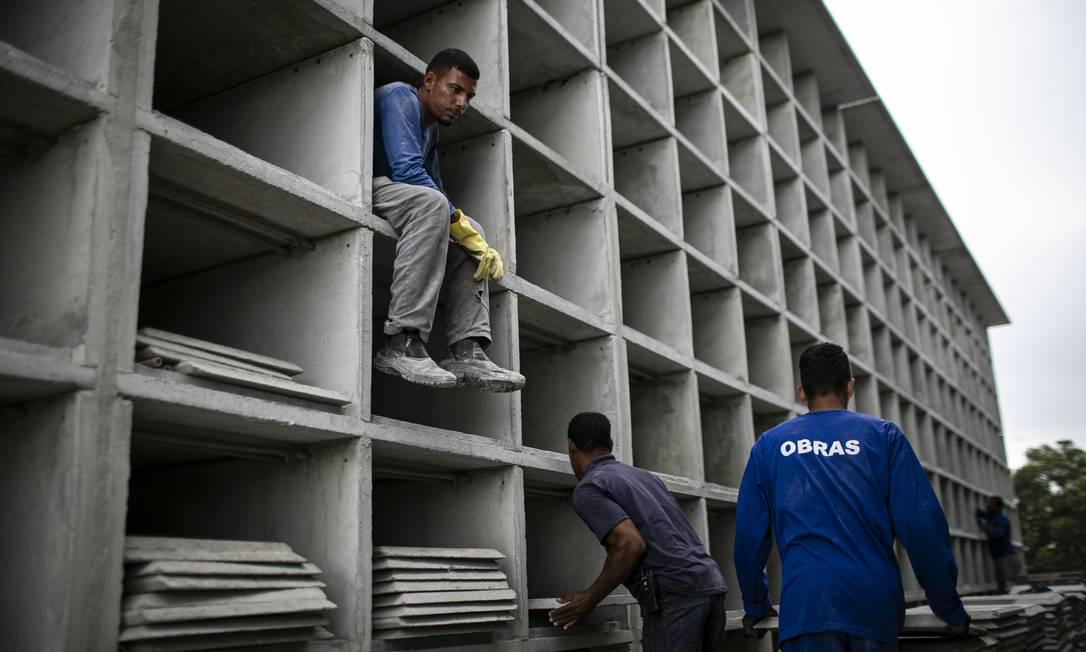 Operários trabalham na construção de novas gavetas para caixões no cemitério do Caju, no Rio, em preparação para possível aumento no número de óbitos por Covid-19 Foto: Hermes de Paula / Agência O Globo