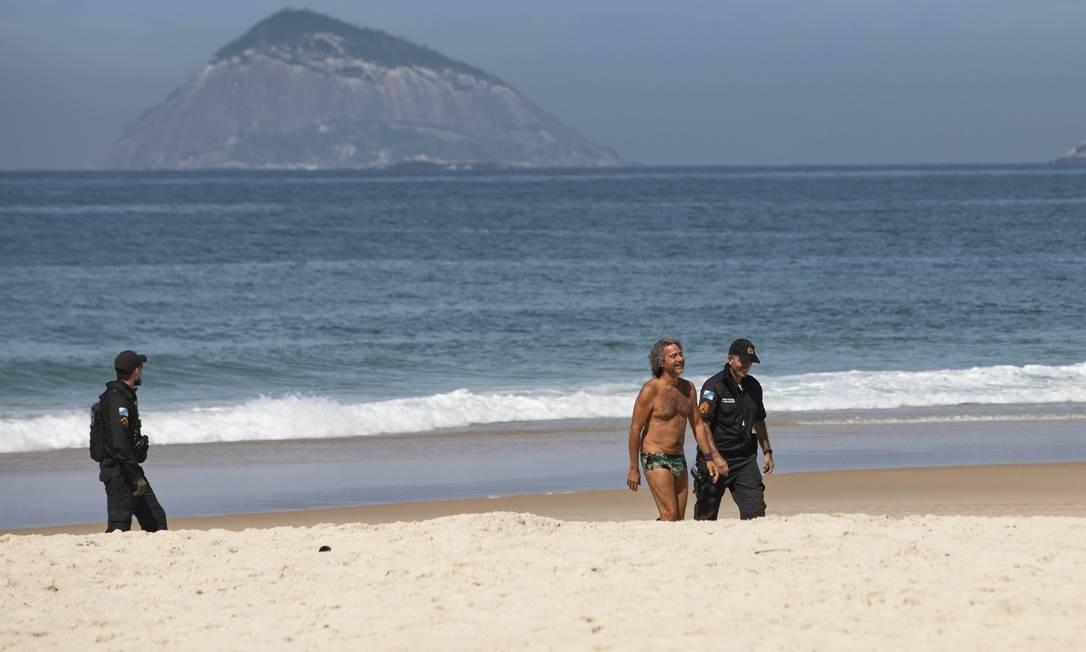 Em domingo de céu parcialmente nublado, cariocas circularam pelo calçadão da orla. Em Copacabana, PM retirou pessoas da areia Foto: Ana Branco / Agência O Globo