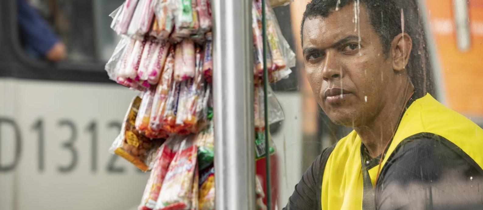 Ambulante Silvio Xavier, 39 anos, em ponto de ônibus, em Padre Miguel. Ele utiliza o transporte público para vender doces Foto: Ana Branco / Agência O Globo