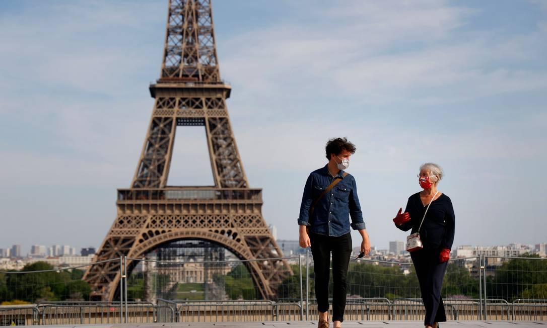 Pessoas com máscara passeiam perto da Torre Eiffel, em Paris Foto: THOMAS COEX / AFP