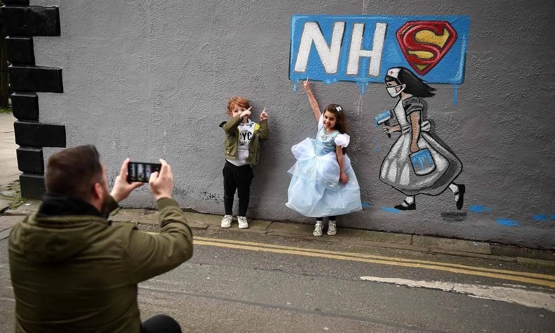 Crianças posam para uma foto junto a um grafite em homenagem ao sistema público de saúde britânico em Pontefract, no norte da Inglaterra AFP Foto: Oli Scarff / AFP