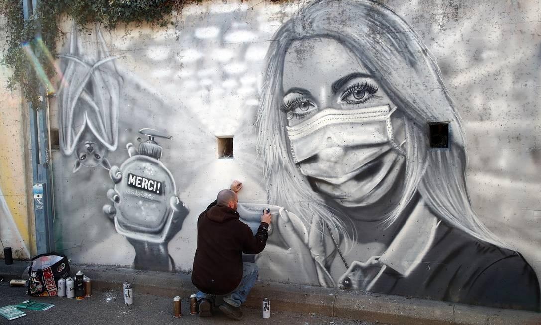"""O grafiteiro David """"S.I.D."""" Perez retoca sua pintura em homenagem aos profissionais de saúde em Gland, na Suíça Foto: Denis Balibouse / Reuters"""