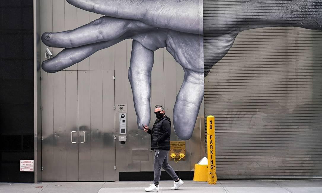 Um homem usando máscara contra o novo coronavírus passa em frente a um grafite em Nova York Foto: Cindy Ord / AFP