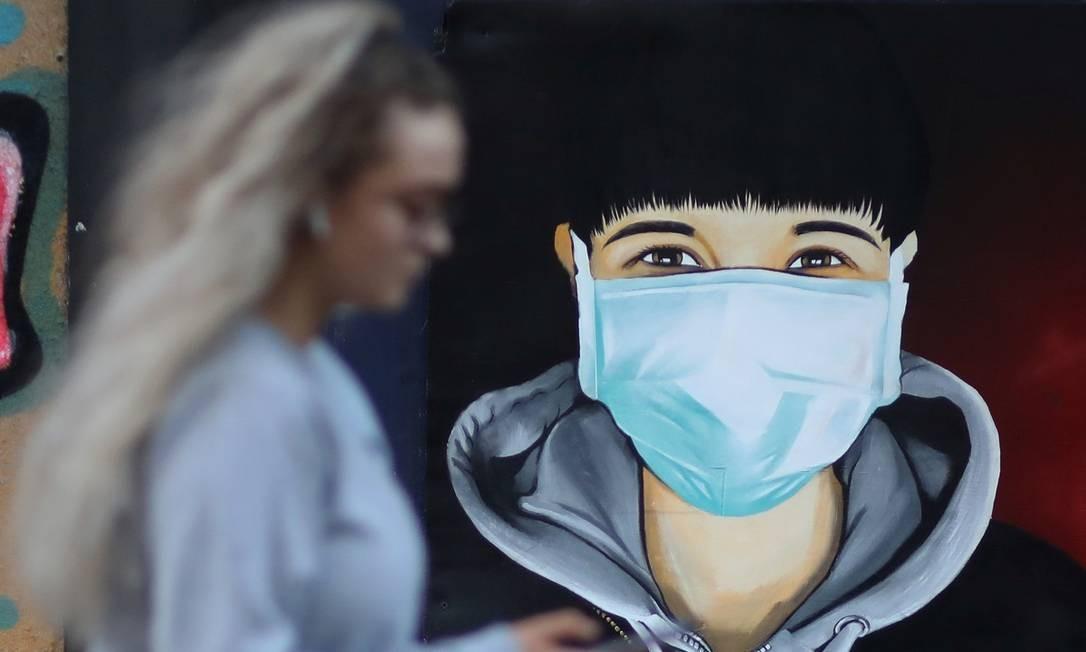 Em Sale, no Reino Unido, uma mulher confere o celular enquanto passa em frente a um grafite que mostra uma figura usando máscara cirúrgica, numa alusão às medidas adotadas contra a pandemia do novo coronavírus Foto: Phil Noble / Reuters