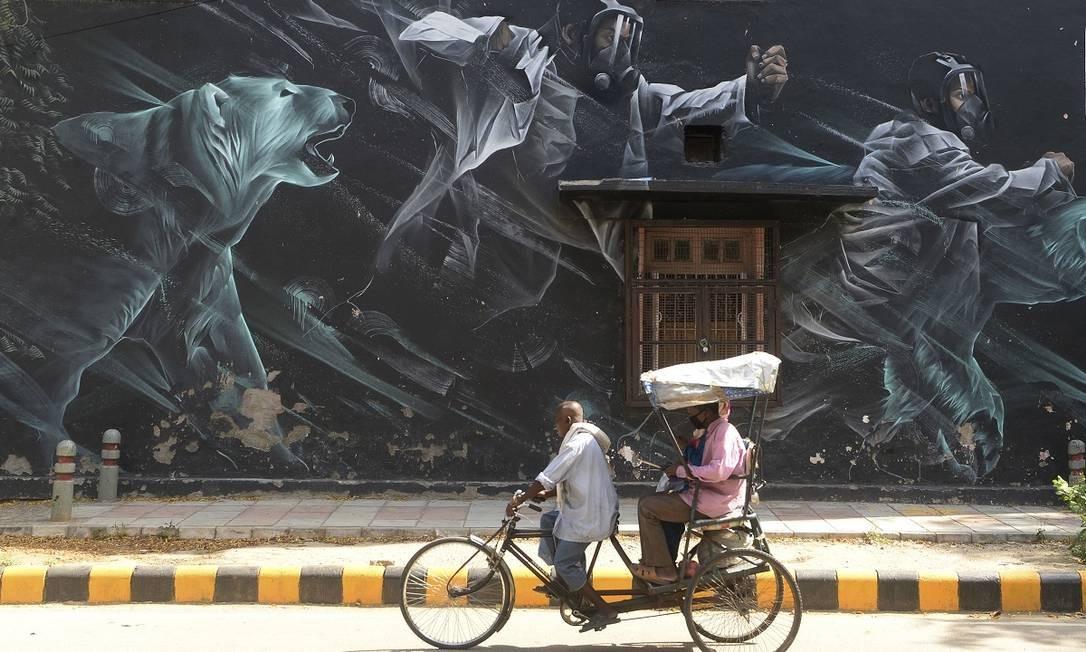Riquixá carregando passageiros usando máscaras cirúrgicas passa em frente a um mural que retrata o combate ao novo coronavírus, no Lodhi Art District, em Nova Delhi, na Índia Foto: Sajjad Hussain / AFP