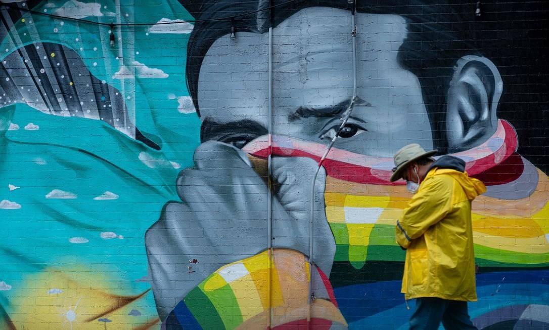 Em Nova York, um homem usando uma máscara para não se infectar com o novo coronavírus caminha em frente a um muro, onde um grafite retrata outro homem cobrindo o rosto Foto: Johannes Eisele / AFP