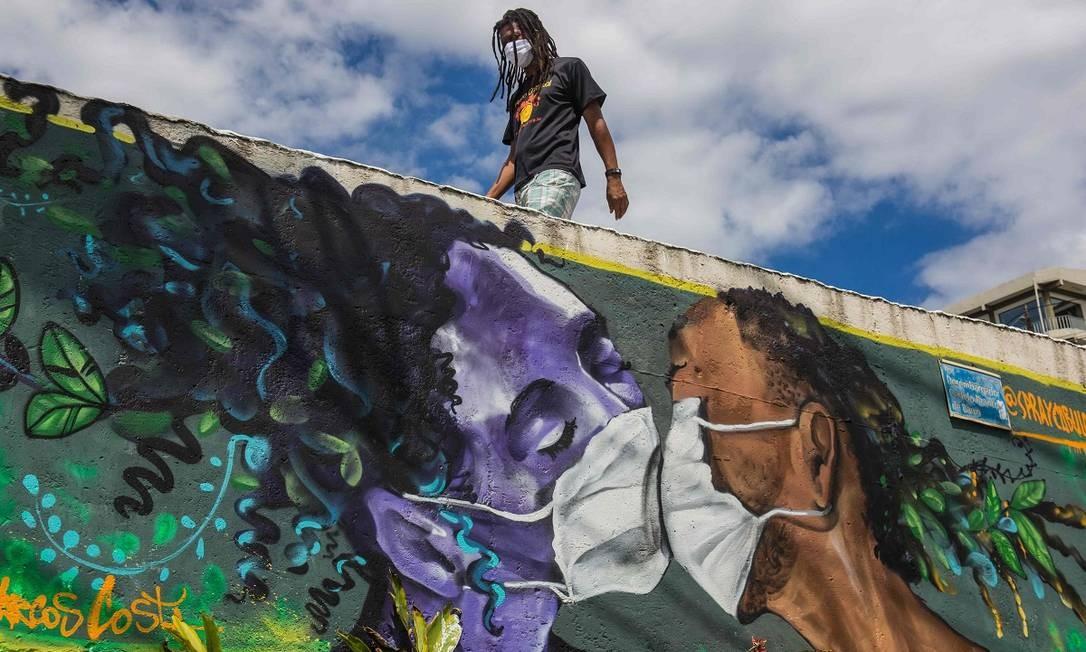 Um homem caminha acima da pintura mural do grafiteiro Marcos Costa, o Spraycabuloso, que mostra um casal usando máscara contra a Covid-19, na entrada da favela do Solar do Unhão, em Salvador Foto: Antonello Veneri / AFP