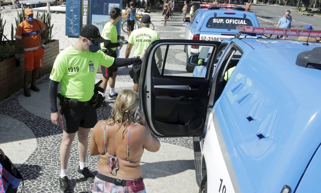 Mulher estava com a família na praia de Copacabana e não respeitou o pedido da PM para sair da água Foto: Gabriel de Paiva / O Globo