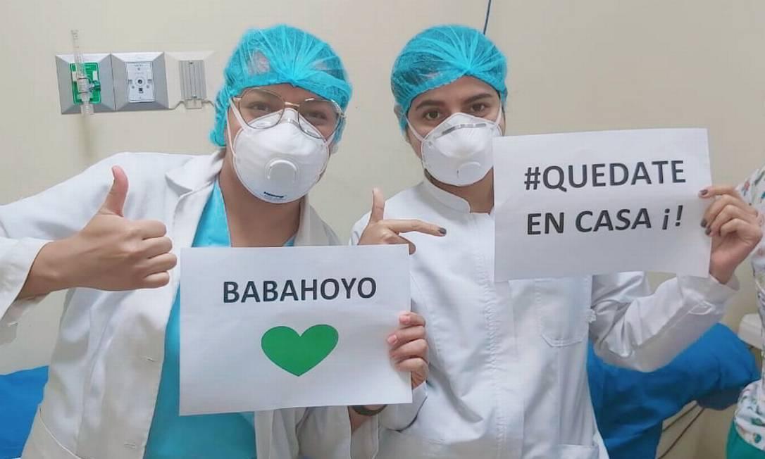 De óculos, médica Julieth Rivera ao lado de colega, com placa que pede para a população ficar em casa Foto: Acervo pessoal