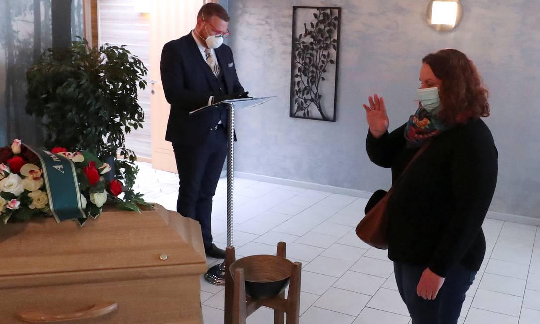 Familiar se despede de parente morto pela Covid-19 na Bélgica Foto: YVES HERMAN / REUTERS